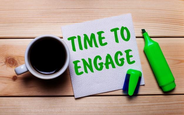 Su un tavolo di legno, una tazza di caffè, un pennarello verde e un tovagliolo con il testo time to engage