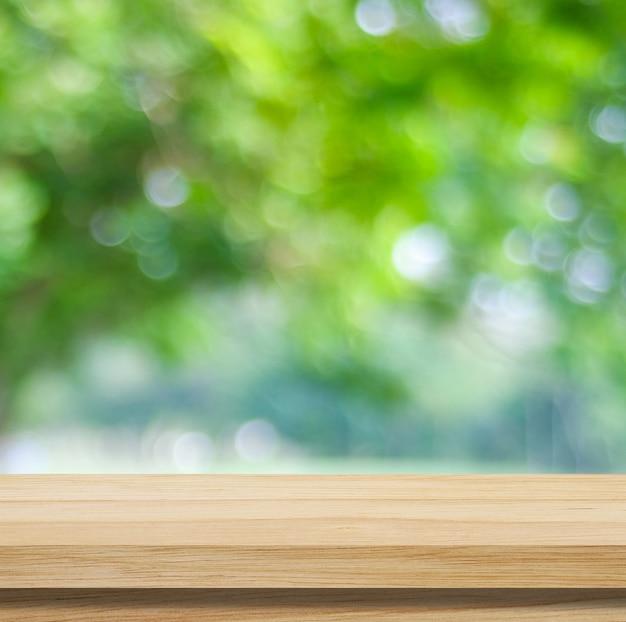 Tavolo in legno per esposizione di prodotti alimentari su sfondo verde sfocato del giardino