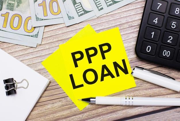 Il tavolo in legno ha una calcolatrice, banconote, una penna, graffette e adesivi gialli con la scritta ppp loan. concetto di affari