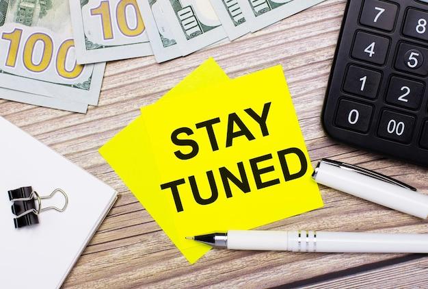 Il tavolo in legno ha una calcolatrice, banconote, una penna, graffette e adesivi gialli con il testo stay tuned. concetto di affari