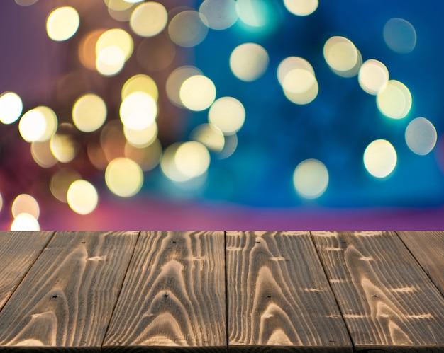 Tavolo in legno mock up con cerchi bokeh garland.
