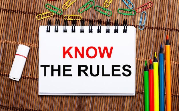Su un tavolo di legno, matite multicolori, graffette, una chiavetta usb bianca e un taccuino con il testo conosci le regole