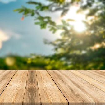 Tavolo in legno in alberi verdi all'aperto natura luce solare display quadrato sfondo