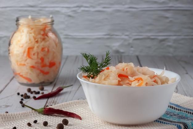 Su un tavolo di legno, crauti con carote e spezie in una ciotola. vista dall'alto orizzontale, stile rustico