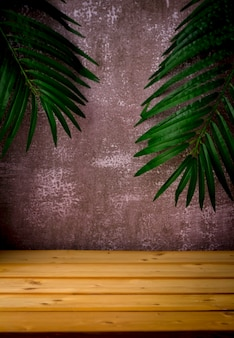 Tavolo in legno per esposizione e presentazione di prodotti da esposizione, foglie di palma e sfondo scuro e robusto