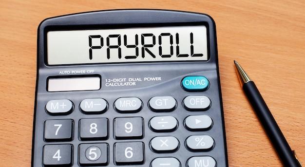 Su un tavolo di legno c'è una penna nera e una calcolatrice con la scritta payroll. concetto di affari