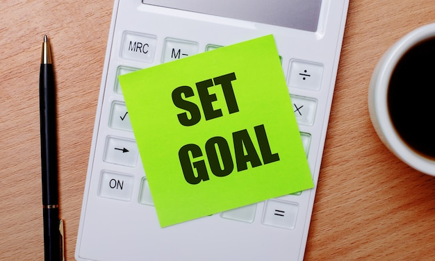Su un tavolo di legno c'è il caffè in una tazza bianca, una penna e una calcolatrice bianca con un adesivo verde con il testo set goal. concetto di affari