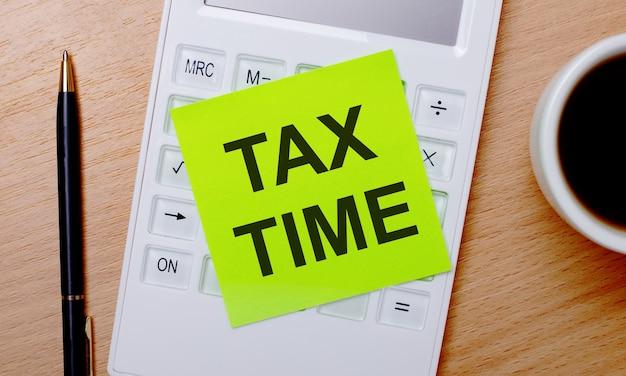 Su un tavolo di legno c'è il caffè in una tazza bianca, una penna e una calcolatrice bianca con un adesivo verde con la scritta tax time. concetto di affari