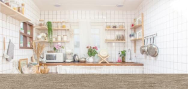 Piano del tavolo in legno sulla stanza della cucina di sfocatura