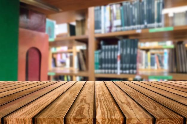 Piano del tavolo in legno su scaffali sfocati libro impilato in biblioteca