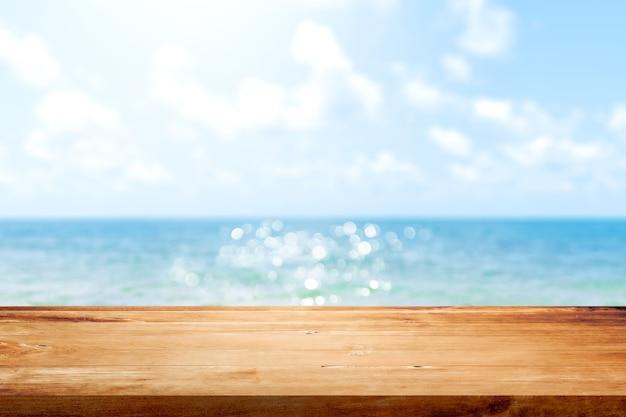 Piano del tavolo in legno su sfondo blu mare e cielo estivo sfocato