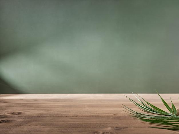 Piano del tavolo in legno su sfondo verde muro