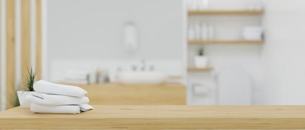 Piano del tavolo in legno con asciugamani da bagno su interni bagno minimalista bianco e legno sfocato 3d