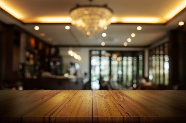 Piano d'appoggio di legno con il fondo interno della caffetteria o del ristorante della sfuocatura