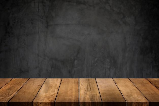 Piano del tavolo in legno con sfondo sfocato parete lucida di cemento scuro.