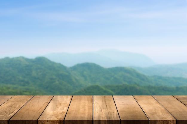 Piano del tavolo in legno con sfondo sfocato di montagna e foresta naturale