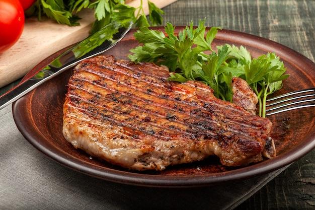 Su un tavolo di legno su un piatto bianco si trova un pezzo di maiale fritto con erbe aromatiche, vista del primo piano