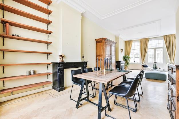Tavolo in legno con sedie nere e decorazioni collocate in una stanza luminosa con grandi finestre in tende eleganti