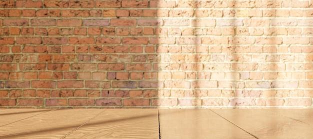 Tavolo in legno con muro di mattoni sfocato con illuminazione della finestra