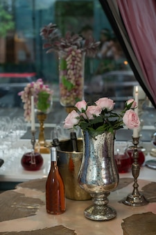 Tavolo in legno con un mazzo di rose in un vaso e una bottiglia di vino. tavolo romantico nel ristorante.