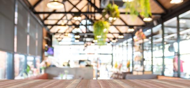 Tavolo in legno con caffè sfondo sfocato.