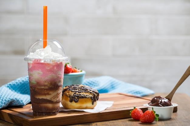 Tavolo in legno con ciambella al cioccolato e un milkshake misto con cioccolato e fragole
