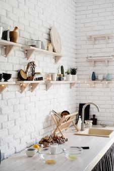Tavolo in legno con diversi utensili da cucina sui colori pastello della cucina rustica bianca