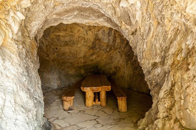 Tavolo in legno con due panche in una stanza in pietra. stanze di pietra della georgia.viaggio in georgia
