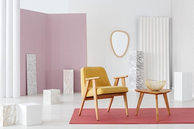Tavolo in legno accanto a una poltrona gialla su un tappeto rosa all'interno del soggiorno retrò con specchio