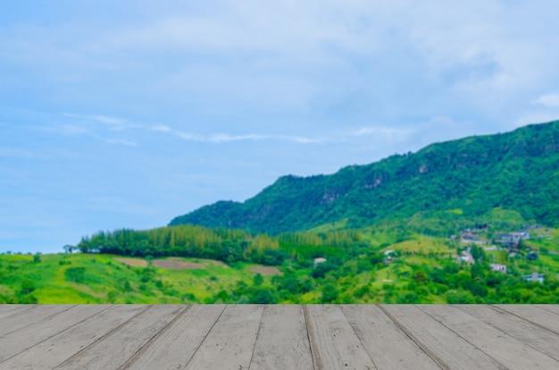 Piano del tavolo in legno con vista sulle montagne e cielo azzurro con nuvole.
