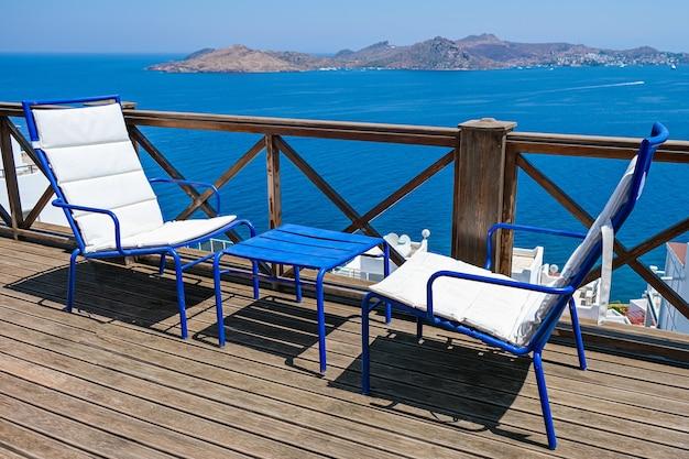Terrazza in legno di villa o hotel con due sedie bianche e tavolo e vista mare.