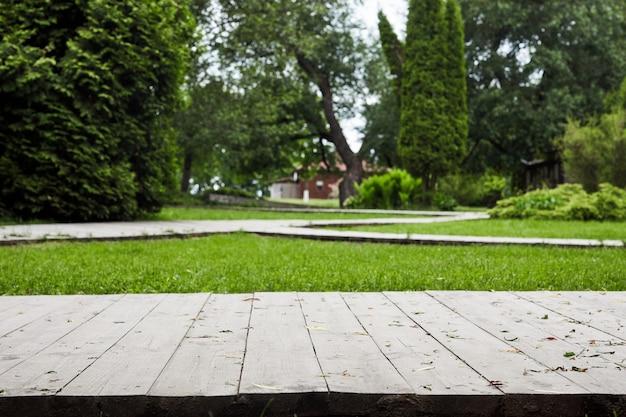 Terrazza o sentiero in legno con prato verde e alberi in cortile o giardino. progettazione del paesaggio del giardino.