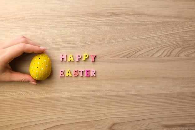 Testo in legno buona pasqua e uovo di legno giallo su un tavolo di legno