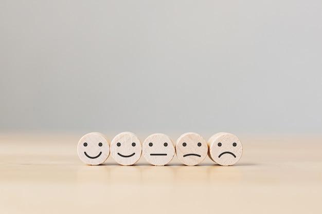 Tre monete in legno con icona faccia, i migliori servizi aziendali eccellenti che valutano l'esperienza del cliente, concetto di indagine sulla soddisfazione