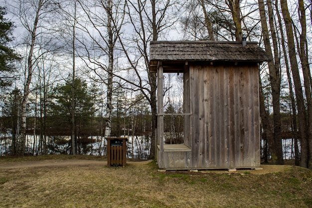 Toilette in legno in natura, vicino agli alberi e a un lago.