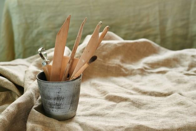 Strumenti di legno per lavorare con argilla e ceramica su uno sfondo di lino in un vetro ceramico