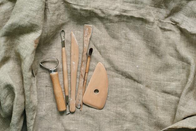 Strumenti in legno per lavorare con argilla e ceramica su uno sfondo di lino