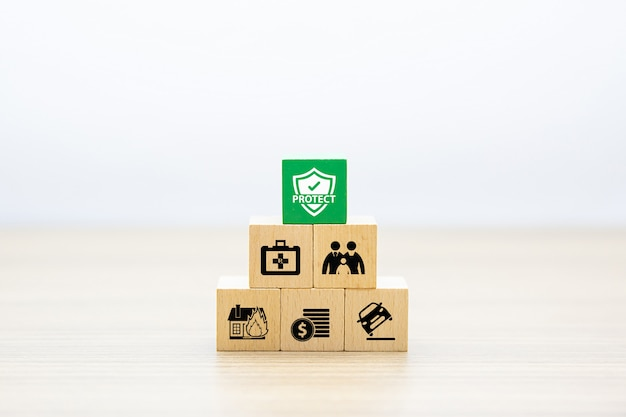 Blocchi giocattolo in legno accatastati a forma di piramide con icona di polizza assicurativa.