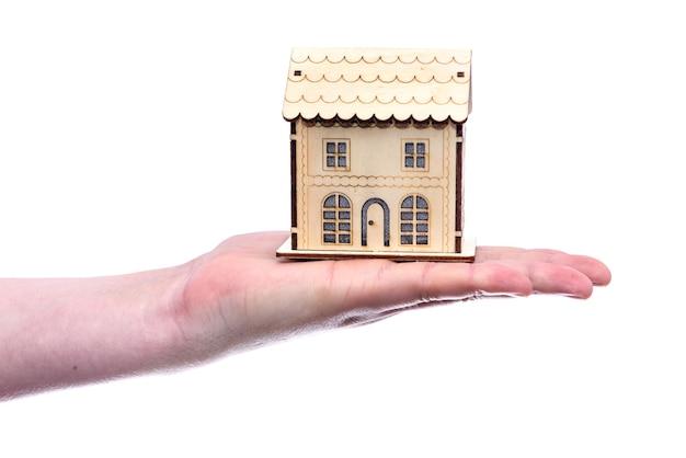 Casa giocattolo in legno sulla mano umana isolata su bianco