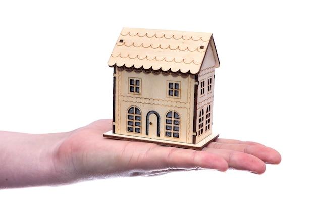 Casa di legno del giocattolo sulla mano umana su bianco