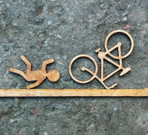 Giocattolo in legno omino e bicicletta. incidente concettuale con ciclista