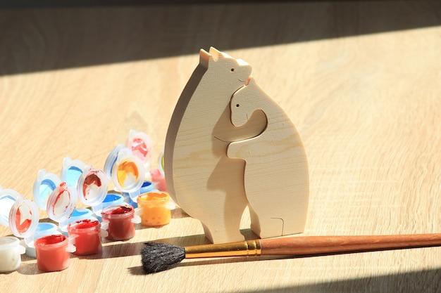 Puzzle giocattolo in legno a forma di animale e vernice colorata su sfondo di struttura in legno