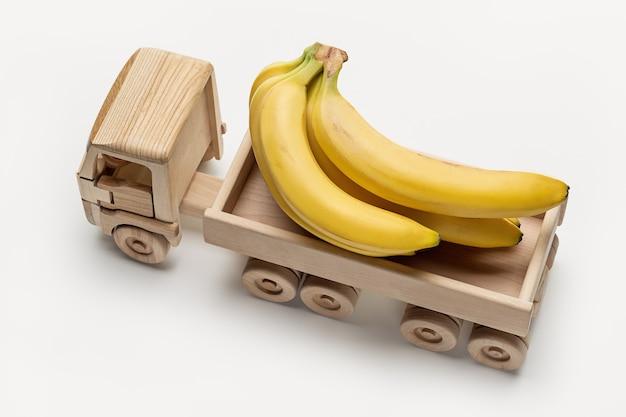 Il camion giocattolo di legno trasporta un mazzo di banane. vista dall'alto, girato in studio.