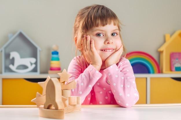 Concetto di giocattoli in legno. bambina sorridente che si siede al tavolo vicino a giocattoli in legno galassia nella stanza dei bambini.