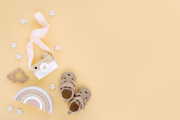 Giocattoli in legno con arcobaleno, macchina fotografica giocattolo e simpatiche pantofole per bambini su sfondo giallo. set di accessori per neonati di genere neutro. disposizione piatta, vista dall'alto