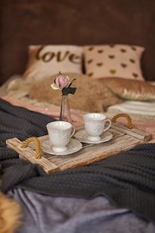 Vassoio in legno di caffè con fiore sul letto. letto romantico con diverse coperte e cuscini caldi. resta a casa, quarantena.