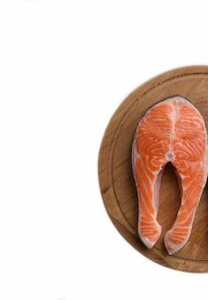 Su un vassoio di legno con sfondo di ritaglio una bistecca di pesce crudo rosso su uno sfondo di ritaglio bianco