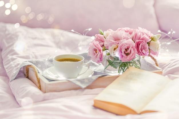 Vassoio in legno con tazza di caffè, libro e fiori di lisianthus rosa