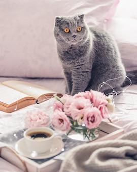 Vassoio in legno con una tazza di caffè, piccoli marshmallow, un simpatico gatto, un libro e fiori rosa di lisianthus