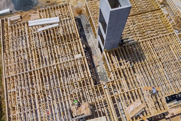 Una capriata di legno sollevata da un carrello elevatore a braccio nei materiali da costruzione una pila